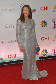 For her Miss Universe Pageant red carpet look, Nina Garcia went for high shine in a long-sleeve, beaded silver gown.