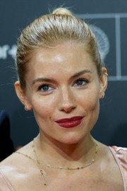 Sienna Miller kept her beauty look subtle except for that striking red lip.