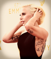 Lady Gaga posed on the Emmy Awards red carpet wearing a revealing dress that exposed her 'Mother Monster' tattoo.