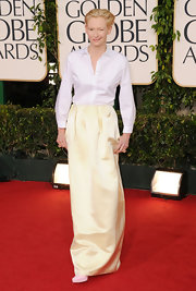 Tilda Swinton opted for an androgynous look at the red carpet in a crisp white button down and lemony skirt by Jil Sander. Pale pink pumps complete the offbeat red carpet attire.