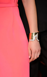 Claire offset her coral Calvin Klein dress with a 1970s gold and diamond cuff.