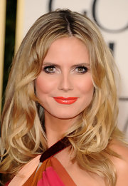 Heidi Klum gets ahead of the pack and dons bright orange lipstick. The Spring 2011 trend is sure to be a hit!