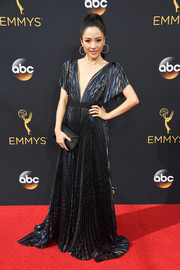 Constance Wu polished off her look with a black envelope clutch.