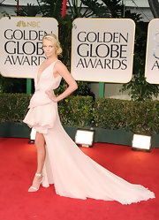 Charlize Theron donned a dramatic cream gown with a high-low hem and voluminous ruffles at the Golden Globes.