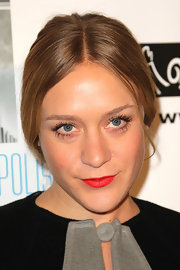 Chloe Sevigny added some spice to her center part bun with classic red lips and defined lashes.