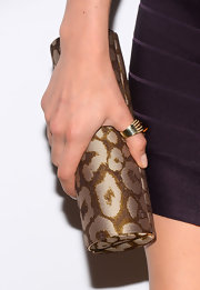 Jessy Schram chose a leopard-print cylindrical clutch to accessorize her purple bandage dress.