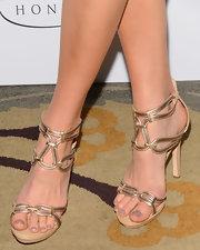 Jessy Schram showed off her pedicure with these gold strappy sandals.