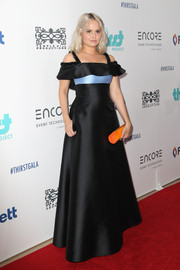 Debby Ryan added a spot of brightness with an orange tube clutch.