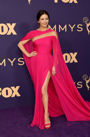Catherine Zeta-Jones caught admiring stares in a caped fuchsia Georges Hobeika Couture gown with an illusion panel and a high side slit at the 2019 Emmy Awards.
