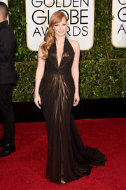 Jessica Chastain went for a gilded-bomshell look in a knot-accented bronze halter gown by Atelier Versace during the Golden Globes.