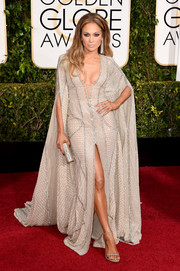 Jennifer Lopez showed off cleavage, legs, and that signature J. Lo diva attitude in a flowing caped gown by Zuhair Murad during the Golden Globes.