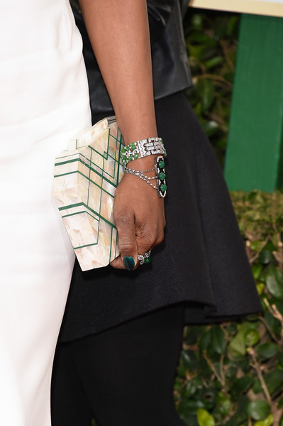 Laverne Cox matched her emerald and silver jewelry to her hard case clutch at the 2016 Golden Globes Awards.