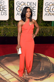 Angela Bassett went modern in a red-orange one-shoulder gown by Safiyaa for her Golden Globes red carpet look.