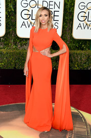 Giuliana Rancic chose an Alex Perry cutout gown in a bold orange hue for her Golden Globes red carpet look.