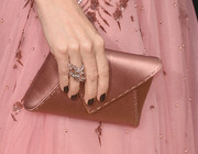 Leslie Mann matched her soft pink dress with a rose gold satin purse at the 2016 Golden Globes Awards.