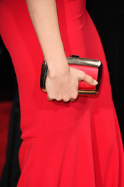 Emmy Rossum went matchy matchy with her bright red clutch that featured gold trimming to complement her Armani Prive gown at the 2016 Golden Globes Awards.