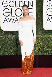 Thandie Newton chose a sleek and sophisticated Monse off-the-shoulder gown, in white with orange sequins along the hemline, for her Golden Globes red carpet look.