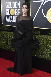 Angelina Jolie looked every inch like Hollywood royalty in a feather-embellished sheer-overlay gown by Atelier Versace at the 2018 Golden Globes.