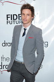 Eddie Redmayne opted for light colors when he paired this gray blazer with a pale blue sweater.