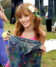 Bella Thorne accessorizes with a green bow and white flower.