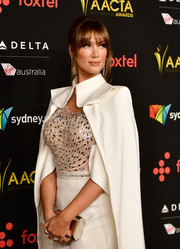 Delta Goodrem paired a geometric gold clutch with a caped jumpsuit for the AACTA International Awards.