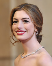 At the 2011 Academy Awards, host Anne Hathaway opted for a classic beauty look: ravishing red lips and a center-parted bun at the nape of her neck. Loose, romantic tendrils frame her face and keep the look from feeling overdone.