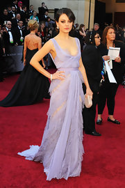 Mila Kunis paired her lovely dress with a nude crocodile clutch by Bottega Veneta.