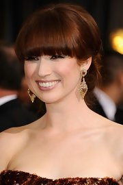 Ellie Kemper attended the 84th Annual Academy Awards wearing her hair in a pretty bobby-pinned updo with heavy lash-grazing bangs.