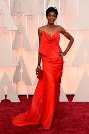 Roshumba Williams slipped into an alluring red cowl-neck gown for her Oscars look.