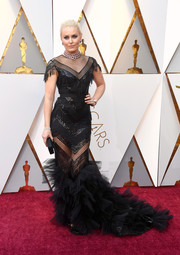 Lindsey Vonn went for vampy glamour in a sheer-panel black Christian Siriano mermaid gown with fringed sleeves and a ruffled hem at the 2018 Oscars.