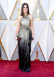 Sandra Bullock made a gorgeous appearance at the 2018 Oscars in a gold and black halter gown by Louis Vuitton.