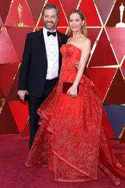 Leslie Mann paired her dress with a box clutch in a deeper shade of red.