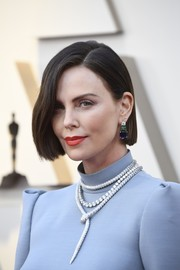 Charlize Theron glammed up her look with an opulent diamond necklace by Bulgari.