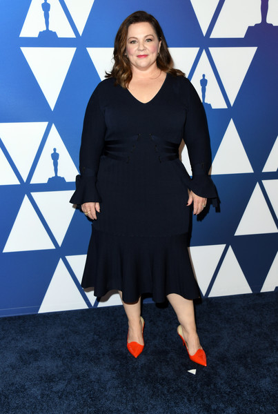 Melissa McCarthy added a bright pop of color with a pair of red mules by Proenza Schouler.