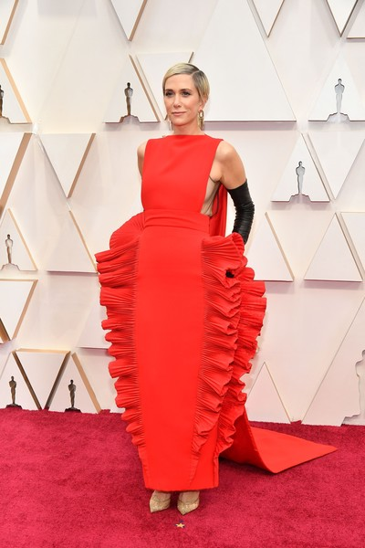 Kristen Wiig looked playfully glam in a sleeveless red Valentino Couture gown with ruffled sides at the 2020 Oscars.