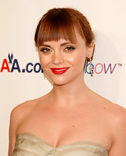 Christina Ricci looked stunning in blunt cut bangs and a simple bun. She finished off her elegant look with a splash of classic red lipstick.