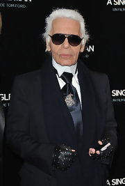 Karl paired his navy tie with a gemstone encrusted brooch.
