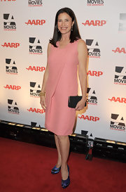 Mimi Rogers offset her sweet pink sheath dress with a black hard case clutch.