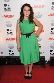 Amara paired her jade green dress with black pumps.