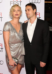 Charlize Theron gave her vintage dress a glam complement with a silver metallic box clutch.