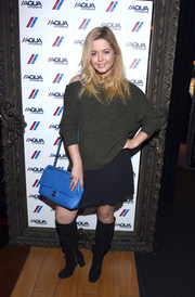 Sasha Pieterse chose a navy mini skirt to pair with her sweater.
