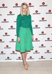 Marissa Mayer paired her sweater with a flared knee-length skirt in a lighter shade of green.