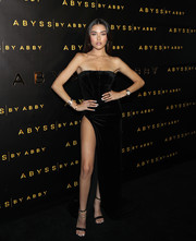 Madison Beer looked sensual in a strapless black corset gown with a hip-high slit at the Abyss by Abby launch.