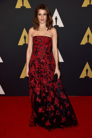 Rachel Weisz exuded classic glamour at the Governors Awards in an Oscar de la Renta strapless gown featuring red floral embroidery on a black background.