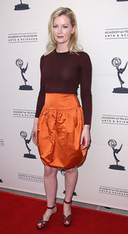 Gretchen Mol paired her carrot orange satin skirt and muted top with burgundy heels featuring bold cutouts and ankle straps.