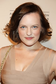 Elisabeth Moss dressed up her classic bob by adding some waves. To try her look, curl one-inch sections of hair away from the face using a medium-barreled curing iron. To add some texture, try backcombing waves slightly and spritzing with a medium-hold hairspray.
