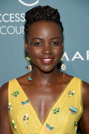 Lupita Nyong'o accessorized with a pair of Carolina Herrera animal and flower earrings to match her cute dress.