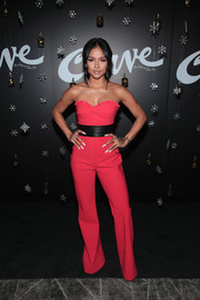 Karrueche Tran stood out on the black carpet in a saturated coral jumpsuit at the Curve Fragrances Holiday Party.