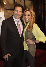 Adrienne Maloof styled up her yellow blouse with a filmy brown vest during her skin care launch.