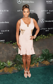 Vivica A. Fox chose a light blush-colored bandage dress with gold embellishments at the waist and bust for her fun and feminine look at the premiere of 'After Earth.'